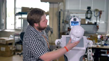 inspection : An engineer takes off a robots face panel. Stock Footage