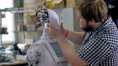 replace : A man attaches screws on a robots head shell.