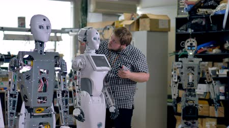 işlenmiş : An engineer installs a back head cover on a robot. Stok Video