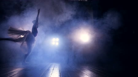 театральный : A female dancer rushes through a dark stage.