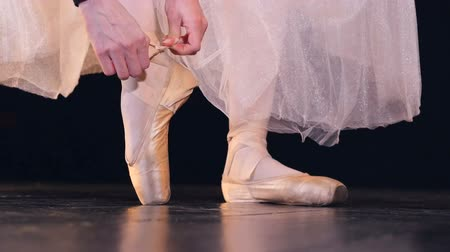 тапочка : Female hands lace up two ribbons on ballet shoes.
