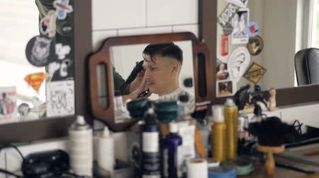 saç kremi : A cluttered hairdressers shelf with a mirror showing salon s client.