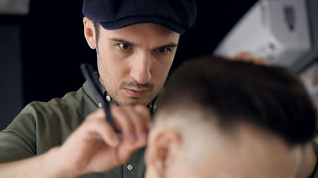бритье : A focused barber uses a straight razor.