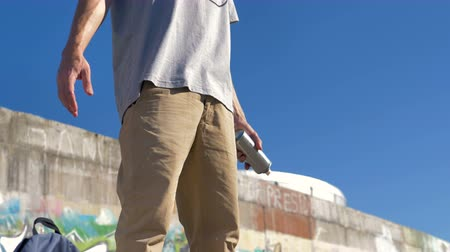 vandalismo : A graffiti artist near a painted wall catches a paint can.