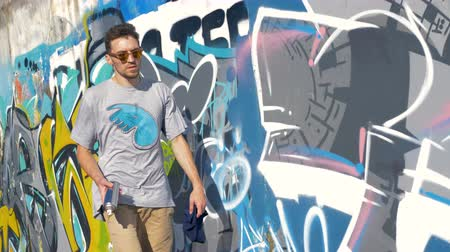 can : A male graffiti artist walks along a painted wall.
