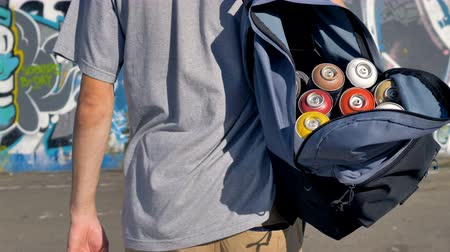 cinematic : An open backpack full of paint cans on graffiti artist shoulder.