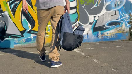 ghetto streets : An open backpack with paint cans hangs from a male hand. Stock Footage