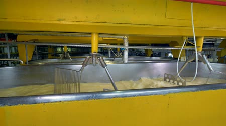 churn : Several rows of yellow milk vats with metal stirrers. Stock Footage