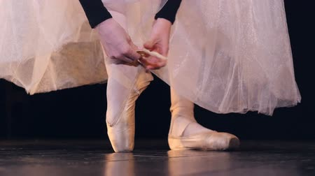 gracefully : A ballerina straps her ballet shoes laces on her ankle.