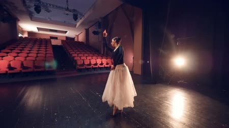 sitting floor : A ballerina turns around in the center of an empty stage.