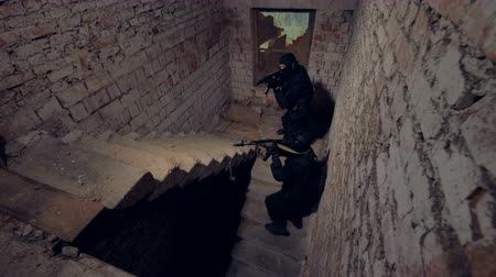 gunman : Two male soldiers ready to shoot enemy at an old stairway. 4K.