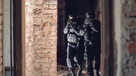 armed : Two swat soldiers explore an abandoned building. Stock Footage
