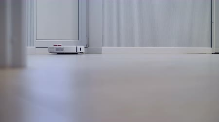 laminált : An automatic wireless robotic cleaner works in a white room. Stock mozgókép