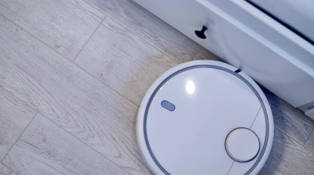 zametání : A robotic vacuum moving along white drawers in a smart house. 4K.