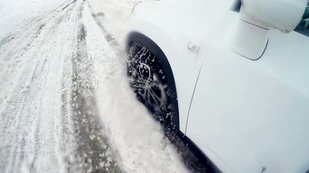 pino : Car wheel slips on a winter snow road. 4K. Stock Footage