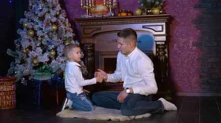acceptance : A man teaches his son a complicated greeting gesture at a Christmas celebration.