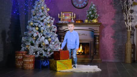 камин : A boy places colorful wrapped presents under a Christmas tree. Стоковые видеозаписи