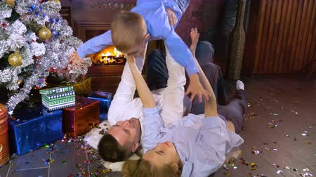 father christmas : Parents lie under a Christmas tree and hold a son above.