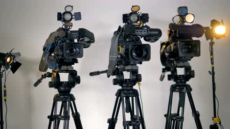 videocamera : A row of several professional cameras on tripods.