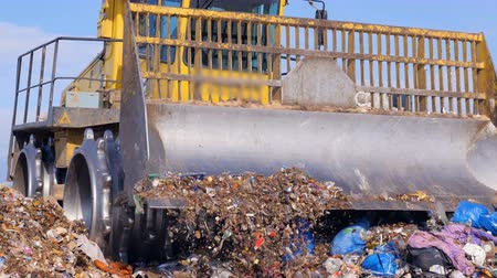 discharging : A close view on a landfill truck near a full garbage truck.