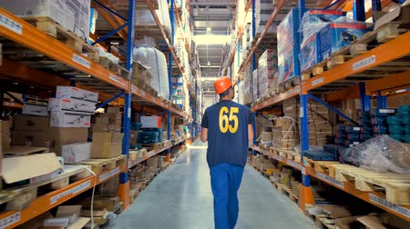 sipariş : A warehouse worker in a hard hat inspects the cargo.