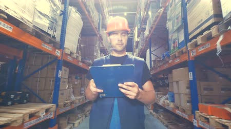 dispatcher : A worker with a clipboard inspects a warehouse.