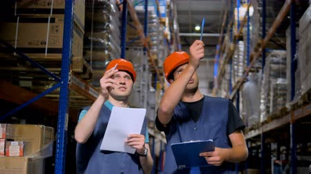 área de trabalho : Two warehouse employees talk and take notes.
