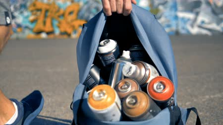 zíper : Several spray cans carried away by a man.
