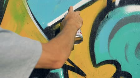 codos : Una mano pinta graffiti en una pared. Archivo de Video