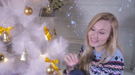 yakın : A woman decorates a Christmas tree on her own. Stok Video