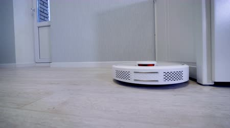 mindennapi : A tracking shot of a round robotic vacuum cleaner.