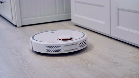 canto : Detailed view on a self-moving robotic vacuum on the floor.