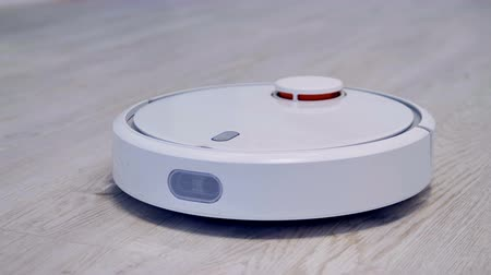 laminált : A robotic vacuum cleaner works on a laminate flooring.