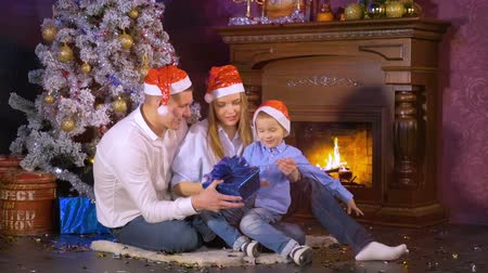 lánya : Happy family open Christmas gifts near christmas New Year fireplace.