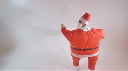 travessura : Santa Claus having fun making funny dancing moves on a white background. 4K. Vídeos