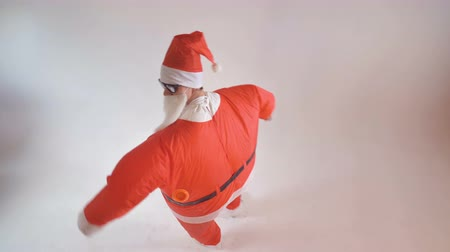 satire : An artist in an inflatable Santa costume greets the viewer.