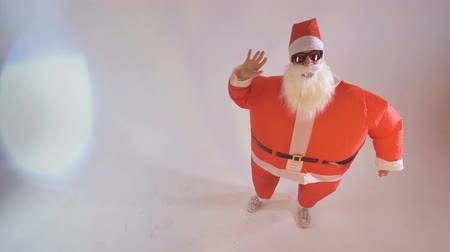 satire : Santa in sunglasses slowly waves both hands.