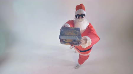 straining : Santa Claus offers a single gift box raising it up. Stock Footage