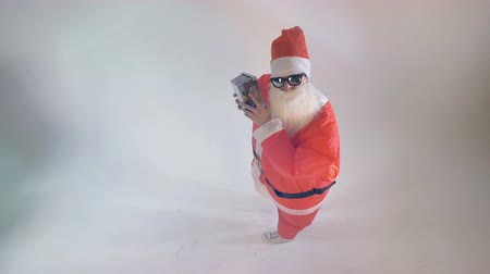 x mas : Santa Claus shakes and offers a gift box. Stock Footage