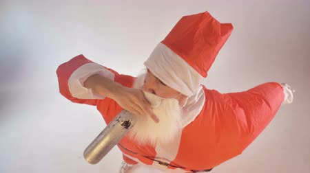 hangover : Santa Claus drinks from a bottle and falls down.