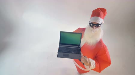 x mas : Santa Claus holds a laptop with green screen and appreciates it. Stock Footage
