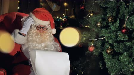 sen : Close-up Santa near decorated christmas tree reading list with christmas wishes.