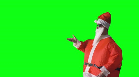 satire : Santa Claus points to an invisible object on a green background.