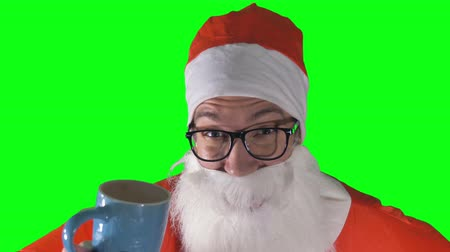satire : A close-up on Santa Claus drinking from a blue mug.