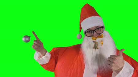 satire : Santa Claus on green background plays with Christmas decorations.