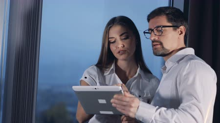 trabalho em equipe : A businessman and a businesswoman discuss their work looking at a shared tablet PC. 4K.