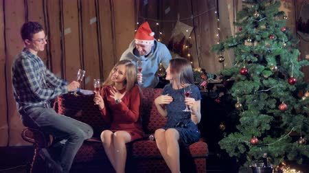 drinki : Close friends celebrate Christmas near a fir tree.