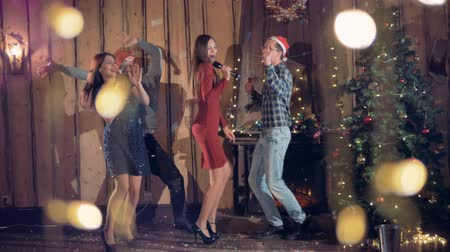 караоке : Four friends dance and sing near a Christmas tree.