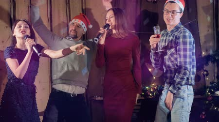 караоке : Two couples enjoy Christmas Eve party dancing and singing together. Стоковые видеозаписи