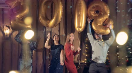 friendship dance : Partying friends hold balloons with number 2018 on strings. Stock Footage